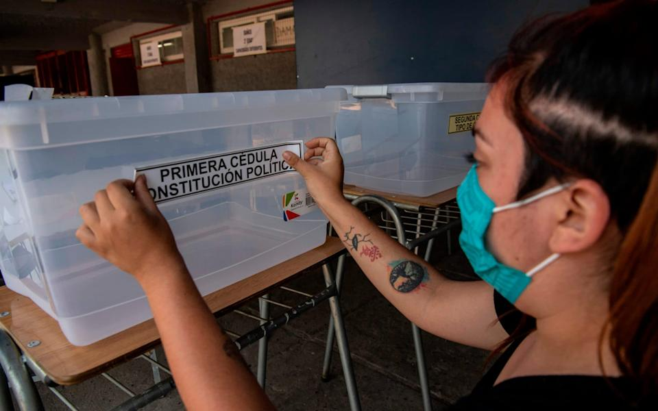 A worker of the Electoral Service of Chile (Servel) sets up a polling station on the eve of a nationwide constitutional referendum voting in Santiago, on October 24, 2020 -  MARTIN BERNETTI / AFP