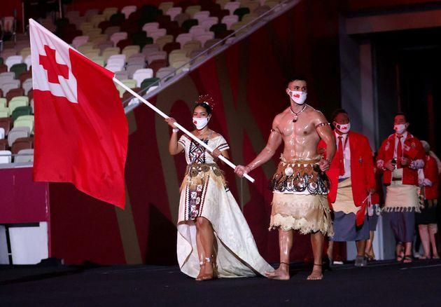 Flag bearers Malia Paseka and Pita Taufatofua of Team Tonga lead their team out during the Opening Ceremony of the Tokyo 2020 Olympic Games. (Photo: Hannah McKay - Pool via Getty Images)