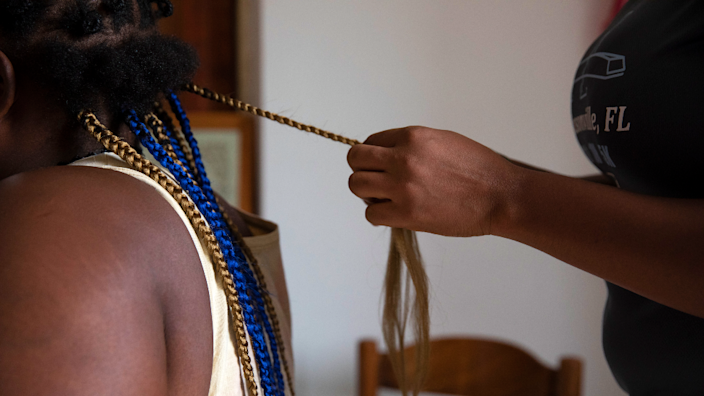 Nigerian woman braids another's hair at a shelter in Sicily after escaping from trafficking networks
