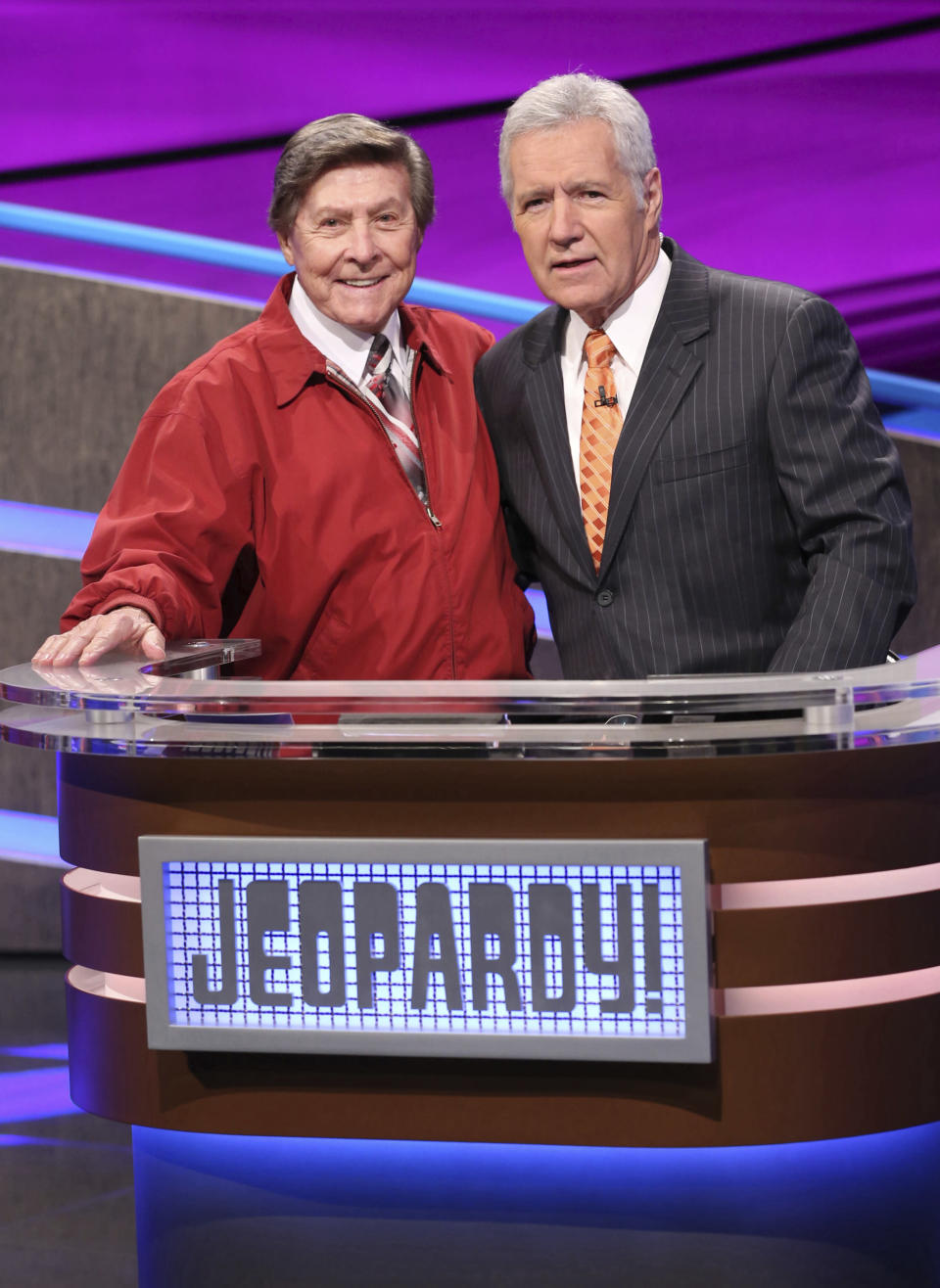 """In this 2014 image provided by Jeopardy Productions, Inc., show announcer Johnny Gilbert, left, and game show host Alex Trebek appear on the set of """"Jeopardy!"""" Gilbert worked with Trebek for 37 years and was reluctant to continue after losing his admired colleague. But others with the show urged him to consider his role as a comforting touchstone for viewers who also were in mourning. (Carol Kaelson/Jeopardy Productions, Inc. via AP)"""