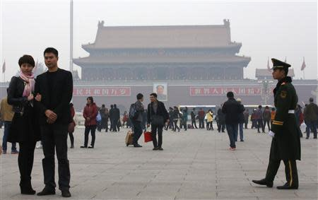 A paramilitary soldier patrols near visitors posing for souvenir pictures at Tiananmen Square in Beijing