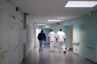 Medical staff of the emergency ward of the Rouvray psychiatric hospital accompany a patient to his room, in Rouen, western France, Wednesday, Nov. 25, 2020. Lockdowns that France has used to fight the coronavirus have come at considerable cost to mental health. Surveying points to a surge of depression most acute among people without work, in financial hardship and young adults. (AP Photo/Thibault Camus)