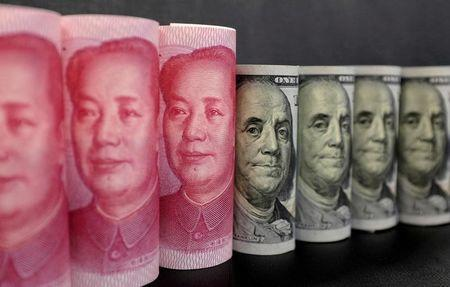 U.S. 100 dollar banknotes and Chinese 100 yuan banknotes are seen in this picture illustration in Beijing, China, January 21, 2016. REUTERS/Jason Lee/Illustration/Files