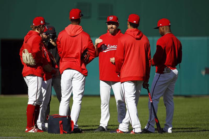 Washington Nationals third base coach Bob Henley, center, speaks with players during a baseball workout, Friday, Oct. 18, 2019, in Washington, in advance of the team's appearance in the World Series. (AP Photo/Patrick Semansky)