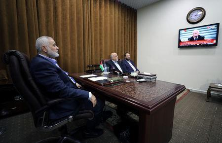 Hamas Chief Ismail Haniyeh watches a TV broadcast of a deal signing between Hamas and Fatah in Cairo, at his office in Gaza City October 12, 2017. REUTERS/Mohammed Salem