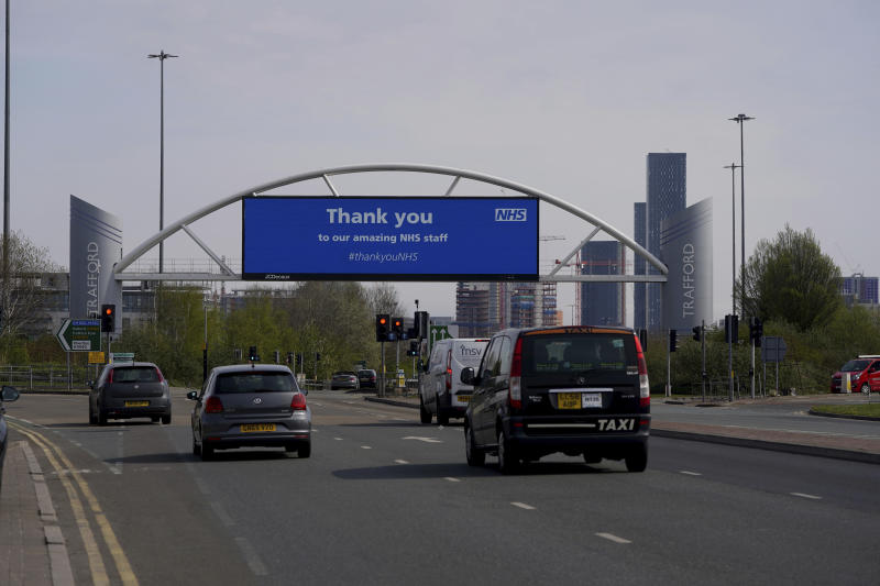 A digital sign thanking NHS (National Health Service) staff is displayed over a road to try to help stop the spread of coronavirus in Manchester, northern England, Thursday, April 9, 2020. The new coronavirus causes mild or moderate symptoms for most people, but for some, especially older adults and people with existing health problems, it can cause more severe illness or death. (AP Photo/Jon Super)