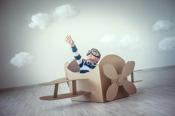 A child playing in a cardboard airplane.