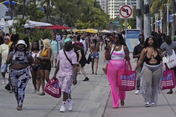 People in a mostly maskless crowd walk down Ocean Drive in Miami Beach, Florida's famed South Beach, Monday, March 22, 2021. A party-ending curfew is in effect in Miami Beach, imposed after fights, gunfire, property destruction and dangerous stampedes broke out among huge crowds of people. The curfew could extend through the end of spring break. (AP Photo/Wilfredo Lee)
