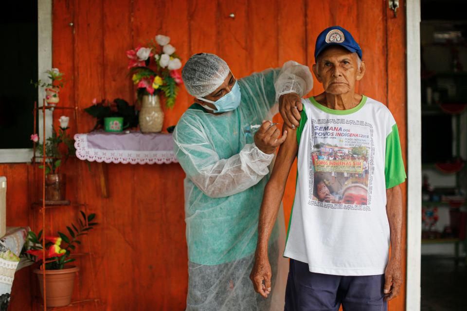 A health worker from the Ministry of Health Department for Indigenous Health adminsters a second doses of a COVID-19 vaccine to a woman in Sao Pedro do rio Arapiun, in the Lower Amazon region of the state of Para, near Santarem in Brazil, on February 15, 2021. (Photo by Tarso SARRAF / AFP) (Photo by TARSO SARRAF/AFP via Getty Images)