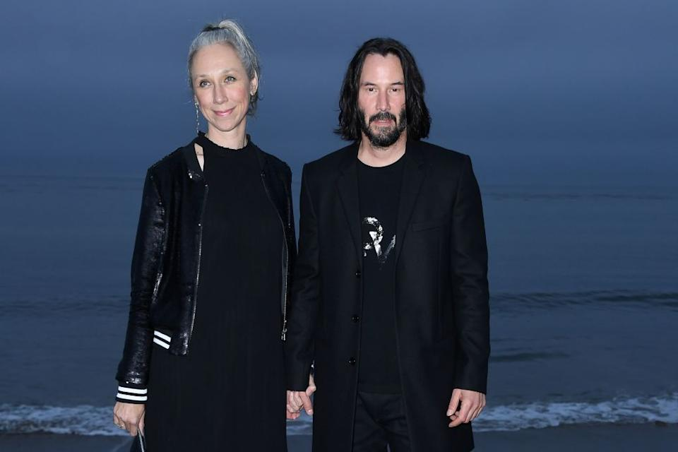 Alexandra Grant and Keanu Reeves hold hands at a June 2016 event. (Photo: Valerie Macon/AFP)