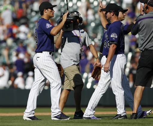 Colorado Rockies thid baseman Nolan Arenado, left, is congratulated by pitcher Roy Oswalt after their 4-3 victory over the Chicago Cubs in a baseball game in Denver, Sunday, July 21, 2013. (AP Photo/David Zalubowski)