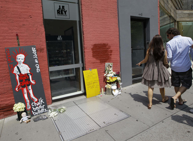 A pedestrian points as she walk past a makeshift memorial to Etan Patz, who was six when he disappeared in 1979, in New York, Sunday, May 27, 2012. The memorial sprung up at the site where, according to police, suspect Pedro Hernandez, now 51, claims the murder took place. The metal sidewalk doors lead to a basement where Hernandez, who was 18 at the time and an employee of a bodega, said he murdered the boy. (AP Photo/Kathy Willens)