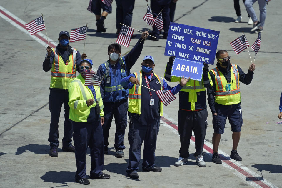 United Airlines employees stand on the tarmac and hold up signs and wave flags during a send-off event for Simone Biles and the U.S. Women's Gymnastics team at the San Francisco International Airport on Wednesday, July 14, 2021. The team was flying to the Summer Olympics in Tokyo. (AP Photo/Eric Risberg)