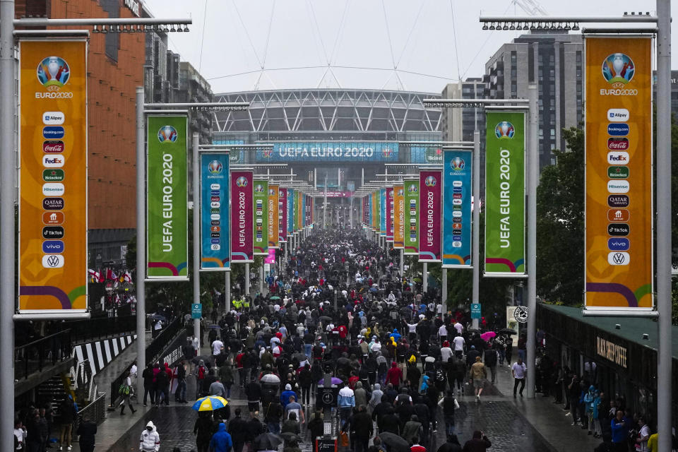Supporters make their way to Wembley stadium in London, Tuesday, June 29, 2021 as they arrive for the Euro 2020 soccer championship round of 16 match between England and Germany. Arguably, no country has elevated sport's role in society quite as much as Britain so the absence of crowds for much of the coronavirus pandemic has been a constant reminder, if any were needed, of the cultural toll of COVID-19. The steady return of fans to sports over the past few weeks and the promise of packed-out stadiums very soon provide hope that life is returning to normal in the wake of the rapid rollout of coronavirus vaccines. (AP Photo/Matt Dunham)