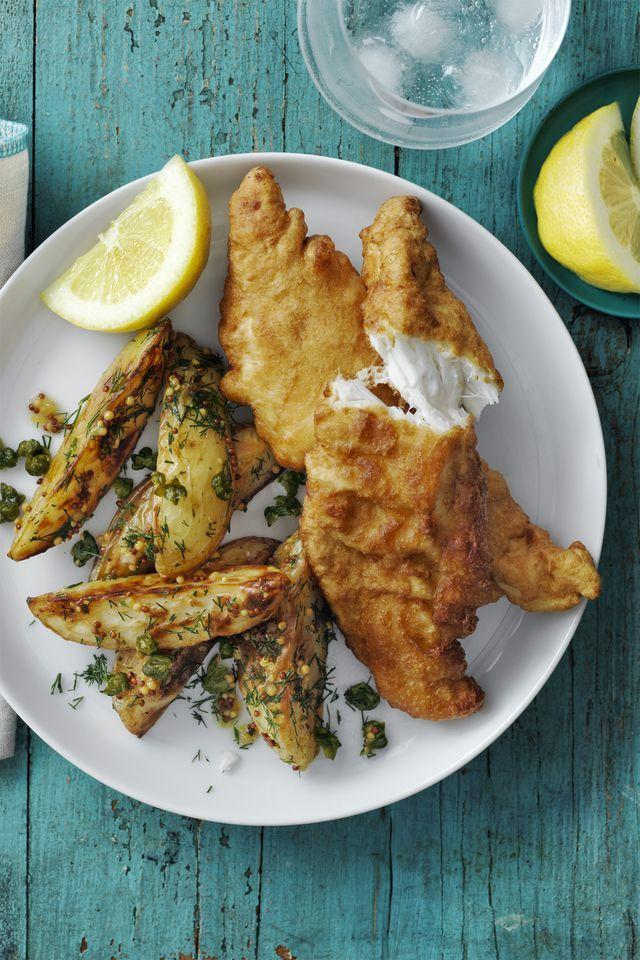 """<p>Fish and chips, anyone? Paired with zesty potato wedges, these fried fish fillets will transport you to a pub in England. </p><p><em><a href=""""https://www.womansday.com/food-recipes/food-drinks/recipes/a58139/beer-battered-cod-roasted-potato-salad-recipe/"""" rel=""""nofollow noopener"""" target=""""_blank"""" data-ylk=""""slk:Get the recipe for Beer Battered Cod and Roasted Potato Salad"""" class=""""link rapid-noclick-resp"""">Get the recipe for Beer Battered Cod and Roasted Potato Salad</a></em></p>"""
