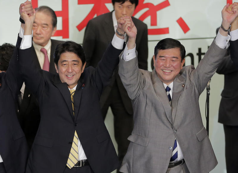 Former Japanese Prime Minister Shinzo Abe, left, joins hands with a contender Shigeru Ishiba after winning the party leadership election of Japan's Liberal Democratic Party in Tokyo Wednesday, Sept. 26, 2012. Abe, known as a hawk and nationalist, defeated ex-defense chief Ishiba in a run-off election Wednesday by a vote of 108-89 to become president of the main opposition Liberal Democratic Party. (AP Photo/Itsuo Inouye)