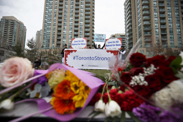 <p>A local Toronto muslim group holds up signs for love and courage for victims of yesterdays crash, at memorial on Yonge St. at Finch Ave. on April 24, 2018 in Toronto, Canada. (Photo: Cole Burston/Getty Images) </p>