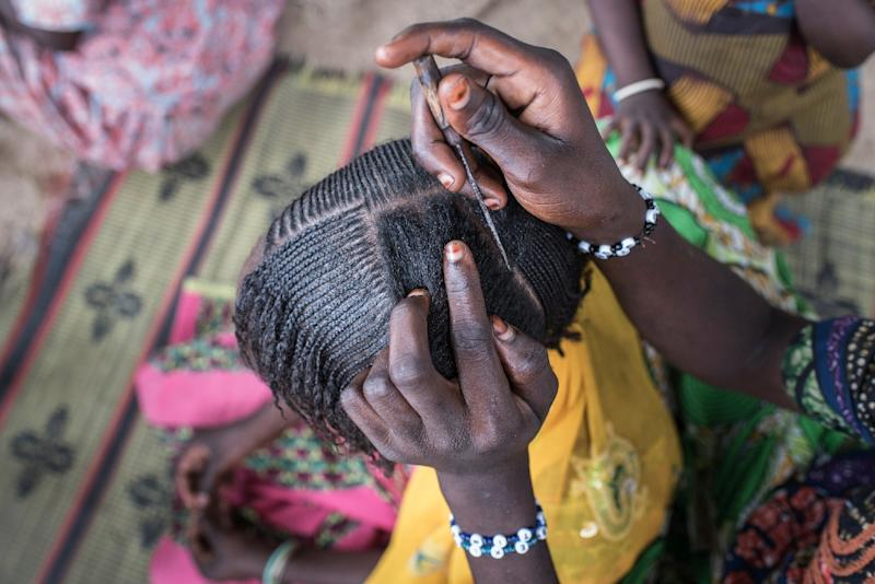 A woman braids a girl's hair at a camp for the internally displaced in northeast Nigeria, where rights groups say women and girls are at serious risk of sexual abuse and rape