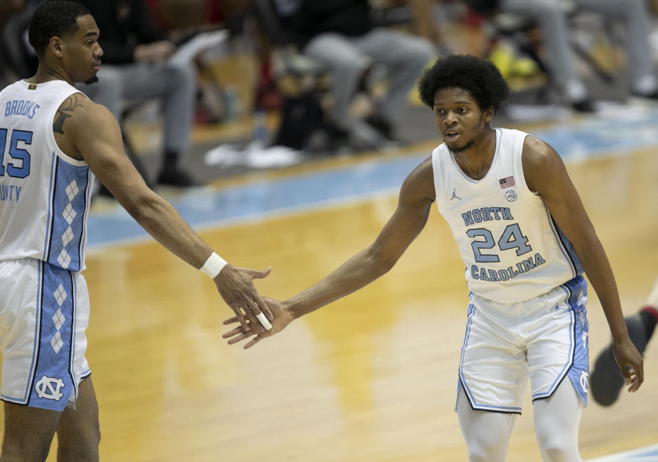 North Carolina's Garrison Brooks (15) congratulates teammate Kerwin Walton (24) after Walton scored his 19th point against Louisville in the second half of an NCAA college basketball game Saturday, Feb. 20, 2021, at the Smith Center in Chapel Hill, N.C. (Robert Willett/The News & Observer via AP)
