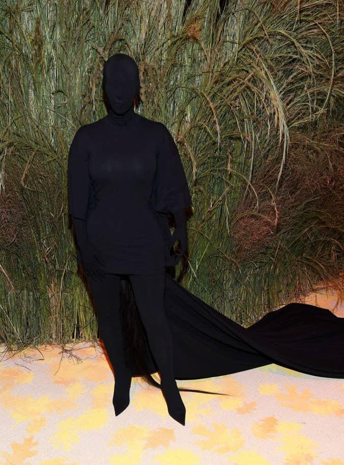 Kim wore a dark long-sleeved dress with matching gloves, tights, and boots and cape. She also wore a full head covering in the same material so that the entire outfit made her look like a shadow