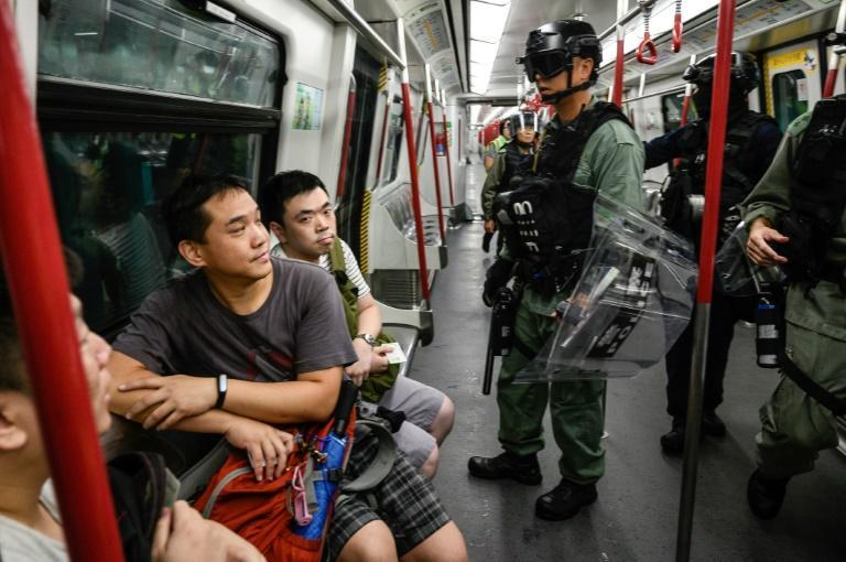 Police check for protesters onboard an underground train in Hong Kong (AFP Photo/Philip FONG)