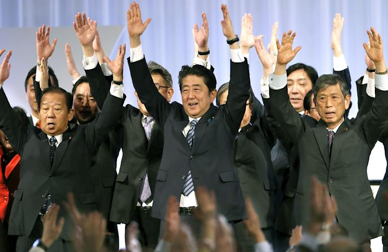 """Japanese Prime Minister Shinzo Abe, center, shouts traditional """"Banzai (long life)"""" cheers with lawmakers and members of his ruling Liberal Democratic (LDP) Party during its annual convention at a hotel in Tokyo, Sunday, March 5, 2017. Japan's ruling party approved a change in party rules Sunday that could pave the way for Prime Minister Shinzo Abe to become the country's longest-serving leader in the post-World War II era. (AP Photo/Shizuo Kambayashi)"""