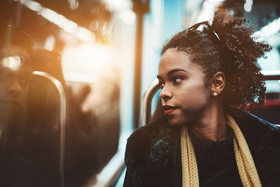 The portrait of a young charming African-American female pensively looking outside the carriage window while sitting indoors of a metro train; Brazilian girl in a subway train, shallow depth of field