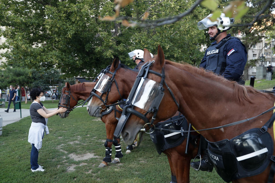 A woman touches a police horse during a demonstration in Belgrade, Serbia, Wednesday, July 8, 2020. Serbia's president Aleksandar Vucic backtracked Wednesday on his plans to reinstate a coronavirus lockdown in Belgrade after thousands protested the move and violently clashed with the police in the capital. (AP Photo/Darko Vojinovic)
