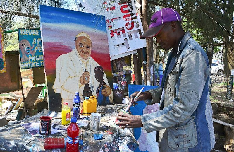 A street artist mixes paint as he works on a painting of Pope Francis in Nairobi, on November 20, 2015 (AFP Photo/Kevin Midigo)