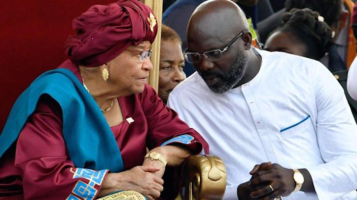 Outgoing President of Liberia Ellen Johnson Sirleaf (left) listens to President-elect of Liberia George Weah during the Weah swearing-in ceremony on January 22, 2018