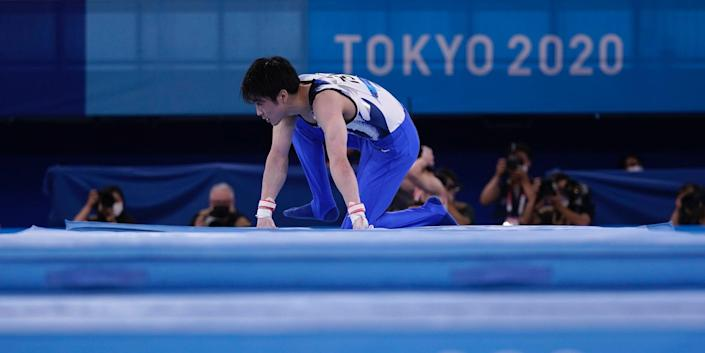 Kohei Uchimura on his hands and knees after falling at the Tokyo Olympics.