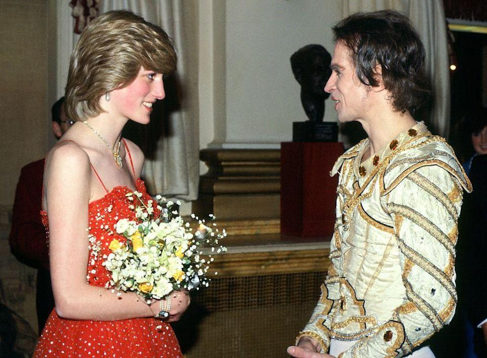 """<p>Princess Diana met famous Russian <a href=""""https://www.townandcountrymag.com/society/tradition/a25919017/princess-diana-kate-middleton-royal-opera-house-ballet-dance/"""" rel=""""nofollow noopener"""" target=""""_blank"""" data-ylk=""""slk:ballet"""" class=""""link rapid-noclick-resp"""">ballet</a> dancer, Rudolf Nureyev, after his performance at the Royal Opera House. He wore his elaborate costume from the performance, while Diana opted for her own striking look in a red tulle dress.<br></p>"""