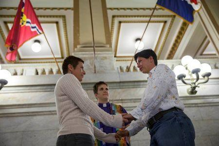 Reverend Katie Hotze-Wilton performs a marriage ceremony for April Breeden (L) and Crystal Peairs (R) at City Hall in St. Louis, Missouri November 5, 2014. REUTERS/Whitney Curtis
