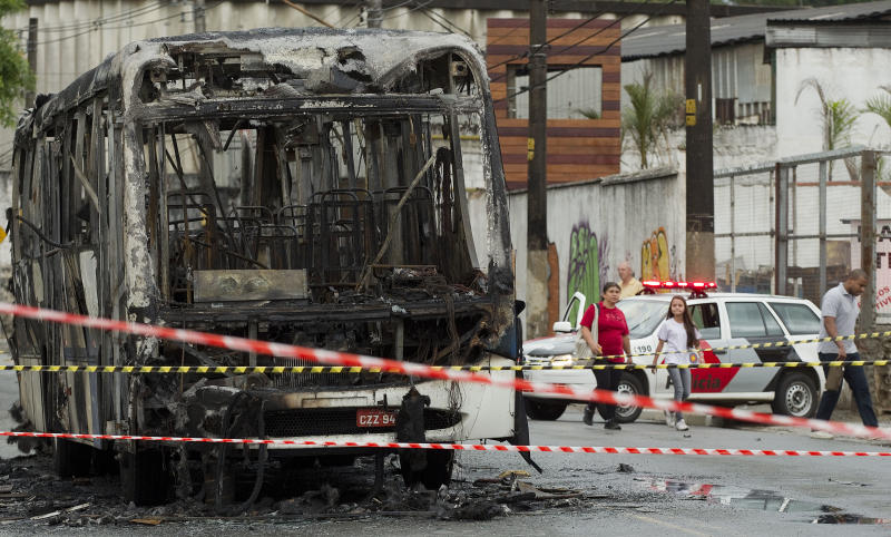 A torched commuter bus is surrounded by police tape in a suburb of Sao Paulo, Brazil, Monday, Nov. 12, 2012. Bus burnings were part of a wave of violence that left 31 dead over the weekend in Sao Paulo, according to police. (AP Photo/Andre Penner)