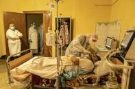 A medical worker treats Mykhailo Kaldarar, patient with COVID-19 as his wife Oleksandra Kaldarar, left, looks at him in a hospital in Rudky, Western Ukraine, on Tuesday, Jan. 5, 2021. Oleksandra Kaldarar shares the room with her husband, Mykhailo, and their son, who are both on ventilators. Ukraine imposed a broad lockdown Friday, but many medical workers in the country fear that it came too late and the long holidays, during which Ukrainians frequented entertainment venues, attended festive parties and crowded church services, will trigger a surge in new coronavirus infections. (AP Photo/Evgeniy Maloletka)