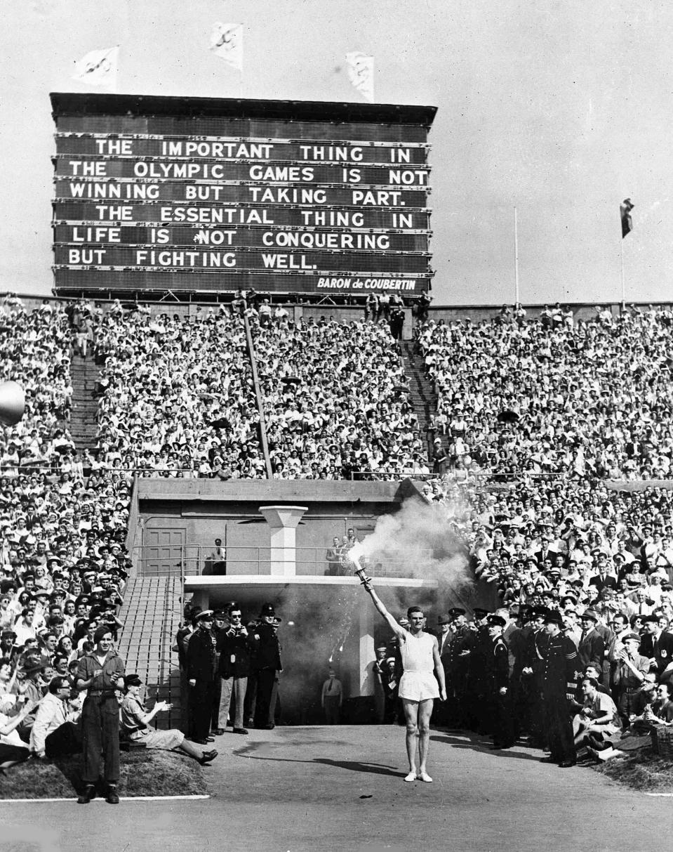 FILE - In this July 29, 1948 file photo, British athlete John Mark holds the Olympic Flame aloft in salute, beneath a quotation from Baron Pierre de Coubertin, founder of the modern games, before making his circuit of the Olympic track during the opening ceremony of the XIV Olympiad, in Wembley Stadium, London. London was still cleaning up bombing damage from World War II when it staged the Olympics in 1948. Britain was also struggling financially; food, clothing and gas were still being rationed. The athletes had to bring their own towels and, with housing in short supply, were accommodated in schools and Royal Air Force camps. The games were organized in less than two years, and despite the tiny budget it was a success, its legacies including greater sporting opportunities for women. (AP Photo, File)