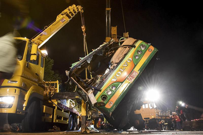 In this photo released by Xinhua News Agency, the wreckage of a crashed tourist bus is lifted on a highway in Taipei, Taiwan Tuesday, Feb. 14, 2017. The bus carrying Taiwanese tourists on a trip to view cherry blossoms flipped over on an expressway ramp in Taiwan's capital on Monday, killing more than 30 people and injuring many others, officials said. (Ou Dongqu/Xinhua via AP)