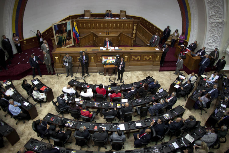 Lawmakers attend a session at the National Assembly in Caracas, Venezuela, Saturday, Jan. 5, 2013. Allies of President Hugo Chavez on Saturday chose to keep Diosdado Cabello as National Assembly president, who is the next in line to step in as a caretaker leader in some circumstances. Chavez's allies hold a majority of the 165 congressional seats. Cabello is sitting at the very top center. (AP Photo/Ariana Cubillos)
