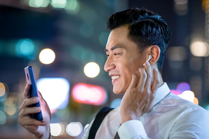 close up of asian man speak to phone by wearing wireless earbuds while walking on the street