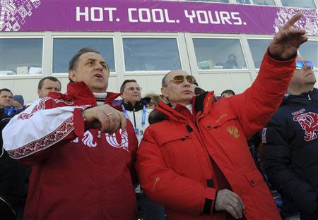Russian President Putin and Sports Minister Mutko watch the cross country skiing men's relay during the Sochi 2014 Olympic Winter Games at Laura Cross-Country Ski and Biathlon Center near Krasnaya Polyana