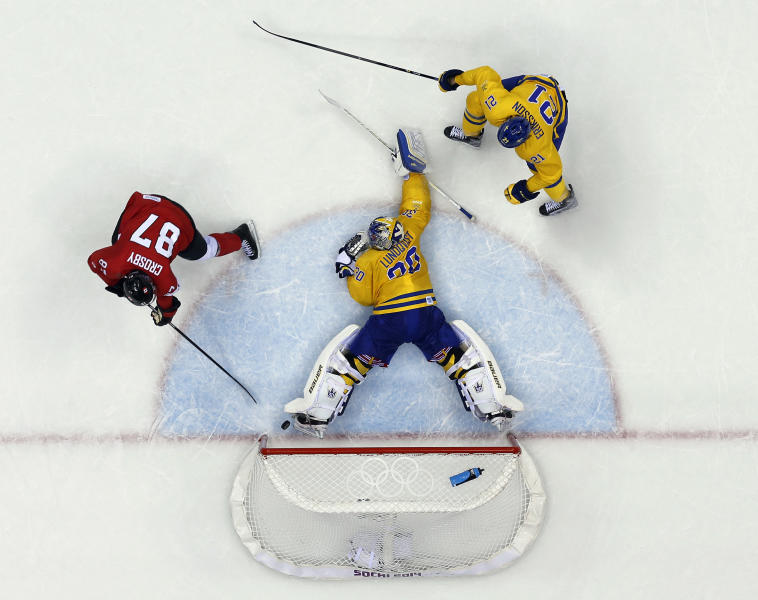 Canada forward Sidney Crosby scores a goal on Sweden goaltender Henrik Lundqvist during the second period of the men's gold medal ice hockey game at the 2014 Winter Olympics, Sunday, Feb. 23, 2014, in Sochi, Russia. (AP Photo/David J. Phillip )
