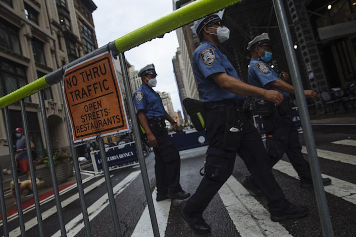 New York Police Department officers walk on a closed section of Broadway in the Flatiron neighborhood of New York, U.S., on Monday, July 6, 2020. (Angus Mordant/Bloomberg via Getty Images)
