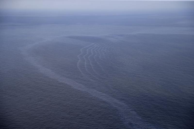 FILE - This March 31, 2015, aerial file photo, shows an oil sheen drifting from the site of the former Taylor Energy oil rig in the Gulf of Mexico, off the coast of Louisiana. A new federally led estimate of oil seeping from a platform toppled off Louisiana 14½ years ago is below other recent estimates. But the report contradicts the well owner's assertions about the amount and source of oil. Oil and gas have been leaking into the Gulf of Mexico since a subsea mudslide caused by Hurricane Ivan on Sept. 15, 2004 knocked over a Taylor Energy Co. production platform.  (AP Photo/Gerald Herbert, File)