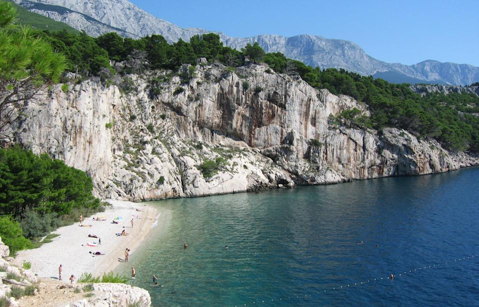 """You'll need to hike down a cliff and tromp through a pine forest for about 40 minutes before you reach Nugal, a pristine beach on <a href=""""https://www.cntraveler.com/gallery/best-places-to-visit-in-croatia?mbid=synd_yahoo_rss"""" rel=""""nofollow noopener"""" target=""""_blank"""" data-ylk=""""slk:Croatia's"""" class=""""link rapid-noclick-resp"""">Croatia's</a> Makarska Riviera. But the spectacular view from the bottom—the beach is flanked dramatically by steep cliffs on either side—and the cool crystalline water make it well worth the trek. Pro tip: Come after a heavy rainfall, and you'll be able to spot a 30-foot waterfall cascading down the northernmost cliff face."""