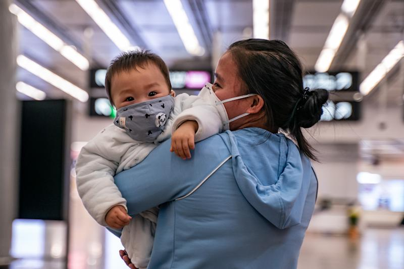 HONG KONG, CHINA - JANUARY 29: A woman carries a baby wearing a protective mask as they exit the arrival hall at Hong Kong High Speed Rail Station on January 29, 2020 in Hong Kong, China. Hong Kong government will deny entry for travellers who has been to Hubei province except for local residents in response to tighten the international travel and border crossing to stop the spread of the virus. (Photo by Anthony Kwan/Getty Images)