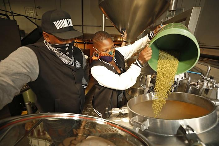 Two people pour hops into a brewing vat.