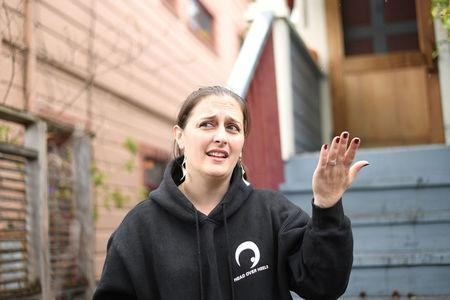 Joy Ashe gestures to a building under renovation outside her home in Emeryville, California, United States March 20, 2017. Ashe, who has spoken before the city's planning commission and city council, is concerned about lead and other pollutants from the construction affecting her family. To match Special Report USA-LEAD/CALIFORNIA REUTERS/Noah Berger