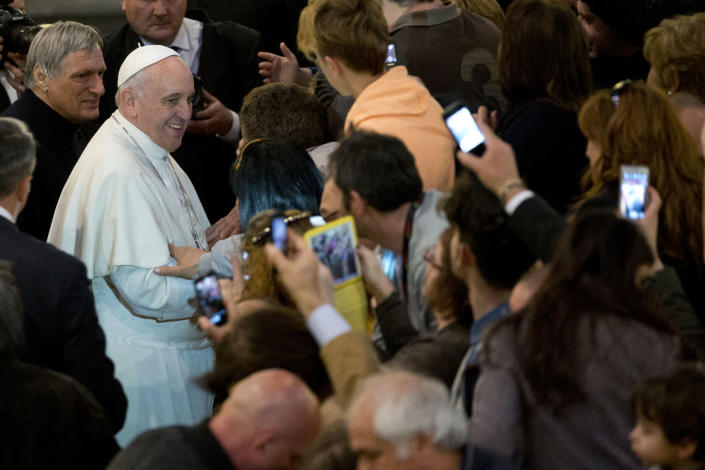 Pope Francis, flanked by Don Luigi Ciotti, left, greets relatives of innocent mafia victims as he arrives for a prayer in Rome's St. Gregorio VII church, just outside the Vatican, Friday, March 21, 2014. (AP Photo/Andrew Medichini)