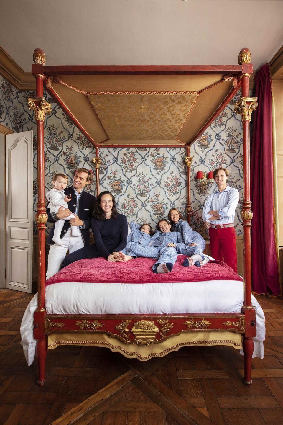 """<p>Preserving the spirit of his 17th-century apartment, decorator Micky Hurley kept the bedroom's original wallpaper, <a href=""""https://www.zuber.fr/en"""" rel=""""nofollow noopener"""" target=""""_blank"""" data-ylk=""""slk:Zuber's"""" class=""""link rapid-noclick-resp"""">Zuber's</a> iconic Petit Parque, in tact. The celebrated print serves as a colorful background from a antique four-poster bed. </p>"""
