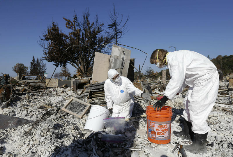 FILE - In this Tuesday, Oct. 31, 2017, file photo, David Rust, left, and his wife Shelly search through the remains of their home destroyed by wildfires in Santa Rosa, Calif. Attorneys representing 14 local governments said Tuesday, June 18, 2019, that they had reached a $1 billion settlement with California utility Pacific Gas & Electric for a series of fires dating to 2015. (AP Photo/Jeff Chiu, File)